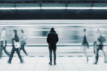 Long Exposure Of Lonely Man At Subway Station With Blurry Train And Walking People