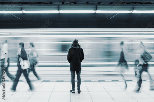 Obraz Long exposure picture with lonely young man shot from behind at subway station with blurry moving train and walking people in background - fototapety do salonu