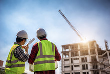 Construction Engineers Discussion With Architects At Construction Site Or Building Site Of Highrise Building With Blueprints.