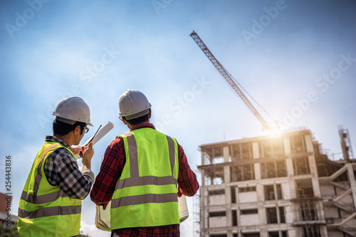 Obraz na plátně Construction engineers discussion with architects at construction site or building site of highrise building with blueprints