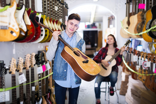 Spoed Foto op Canvas Muziekwinkel Teenagers examining guitars in shop