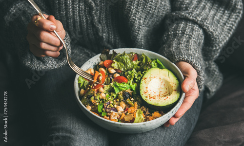 Cadres-photo bureau Nourriture Healthy vegetarian dinner. Woman in jeans and warm sweater holding bowl with fresh salad, avocado, grains, beans, roasted vegetables, close-up. Superfood, clean eating, vegan, dieting food concept
