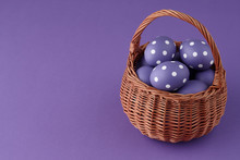 Wicker Basket With Purple Painted Easter Eggs With Dots