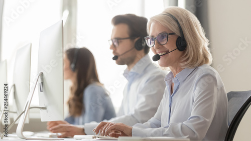 Stampa su Tela Smiling old female call center agent in headset consulting client
