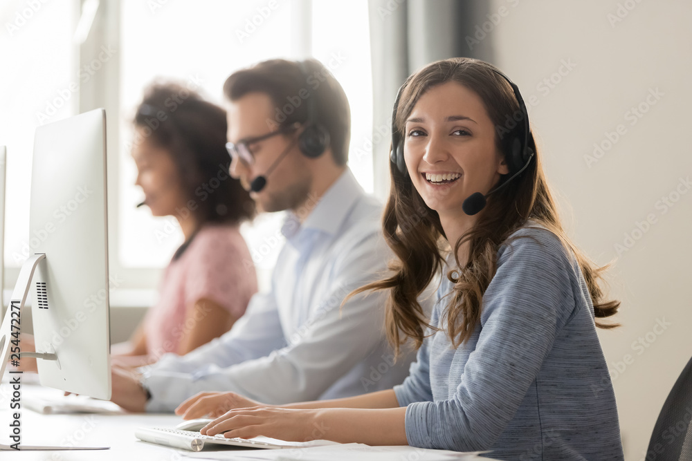 Fototapeta Happy businesswoman call center agent looking at camera at workplace