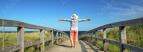 aktive Frau genießt die Auszeit am Strand Fototapete