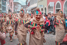 Group Of Friendly Carnival Figures, Figure In The Middle Has A Ratchet In His Hand. Carnival In Southern Germany - Black Forest.