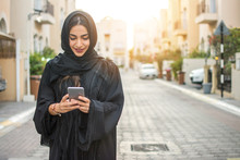 Beautiful Arabian Young Woman In Abaya Using Phone Outdoors In Compound Village.