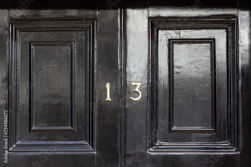 Unlucky house number 13 on a black wooden door Canvas Print