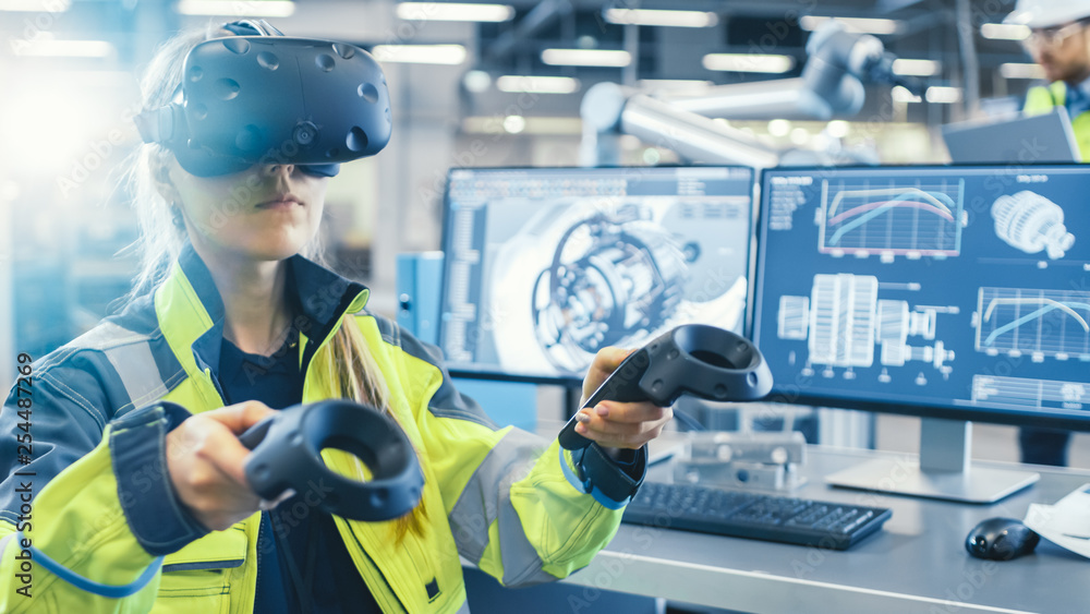Fototapeta Factory: Female Industrial Engineer Wearing Virtual Reality Headset and Holding Controllers, She Uses VR technology for Industrial Design, Development and Prototyping in CAD Software.