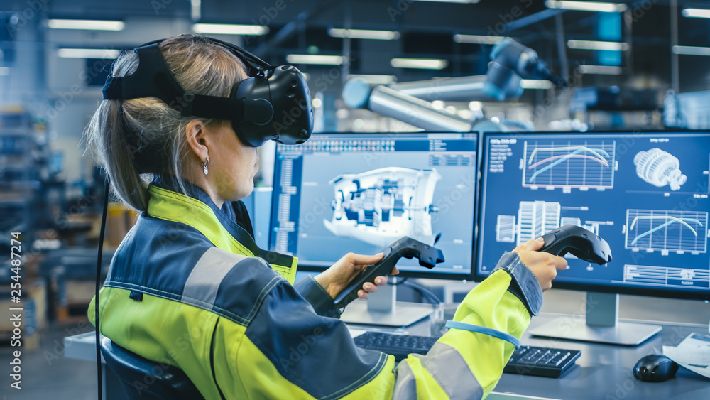 Fototapety, obrazy: Factory: Female Industrial Engineer Wearing Virtual Reality Headset and Holding Controllers, She Uses VR technology for Industrial Design, Development and Prototyping in CAD Software.