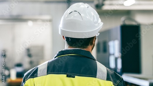 Recess Fitting F1 Back View Shot of the Industrial Engineer Wearing Protective Clothing Walks Through Modern Manufacturing Facility with Automatic Machinery Working in Background.