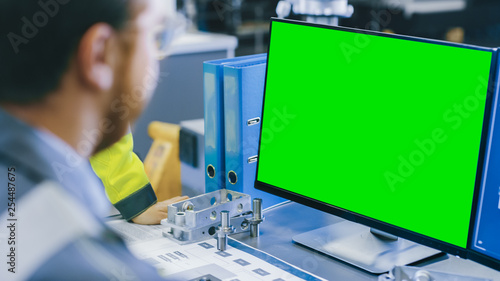 Close-up Back View of the Mechanical Engineer Working on Personal Computer with Green Screen Mock up GReat for Template. Professional Working At the Factory. - 254487675