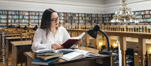 Fotografia Frustrated female student sitting at the desk with a huge pile of study books in