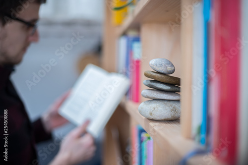 Photo  Feng Shui: Stone cairn at home in a book shelf, man reading in a book in the blu