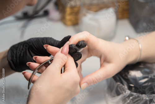 Fotobehang School de yoga Nail care and manicure. Closeup woman in a beauty salon receiving a manicure by a beautician master. Manicurist cutting with nippers client's nails.