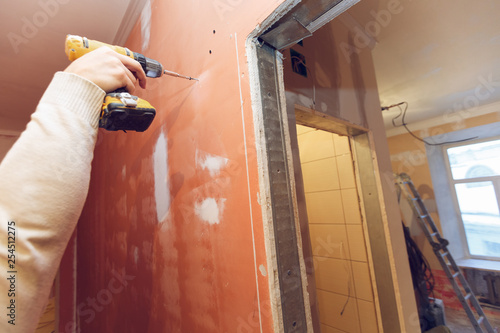 Fotografie, Obraz  Worker is screwing the drywall screw by screw gun to the plasteboard wall in apartment is inder construction, remodeling, renovation, overhaul, extension, restoration and reconstruction