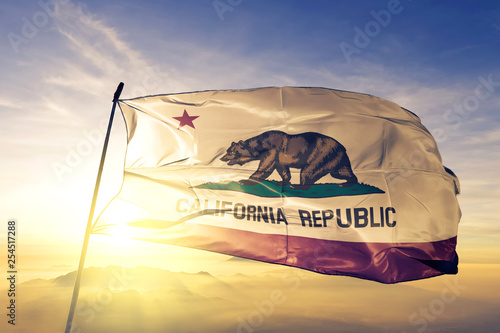 Fototapeta California state of United States flag waving on the top sunrise mist fog