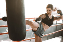Young Woman Trains In Boxing Ring With Heavy Punching Bag. Portrait Of A Sexy Fashion Model Workout In Loft Vintage Gym. Foot Kicks Or Knee Strike.