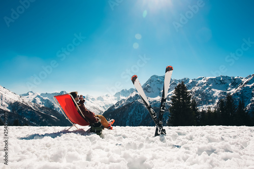 guy chilling out on the slope after skiing in Aprica ski resort with his skies n Wallpaper Mural