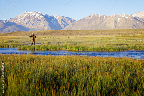 Fotografie, Tablou One man fly fishing on the Owens River at sunrise with the Sierra Nevada Mountai