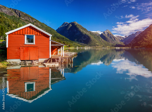 Papiers peints Arctique Beautiful fishing house on fjord. Beautiful nature with blue sky, reflection in water and fishing house. Norway