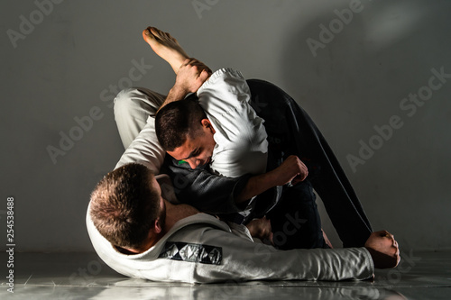 Fotografie, Obraz  Brazilian Jiu Jitsu BJJ training sparring fight triangle submission
