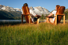 Couple In Adirondack Chairs By June Lake With Sierra Nevada Mountains In Distance
