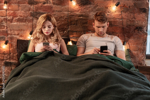 Photo sur Toile Kiev Couple addicted to social media lying in bed and using smartphones