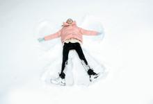 Teenage Girl Making Snow Angel On Winter Day