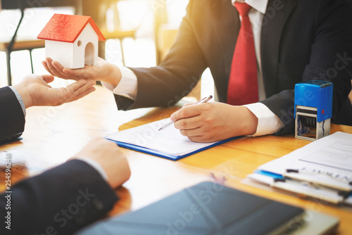 House real estate sell agent reviews the documents that have been approved for the home buyer loan Wallpaper Mural