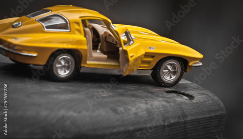 Foto auf Leinwand Toy car model Corvette Sting Ray 1963 year. Yellow color. Side view. Opened door. Close-up. Macro. Isolated.