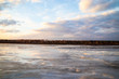 The descent of ice in the spring on the river in March is a natural phenomenon against the sky and clouds in the evening.