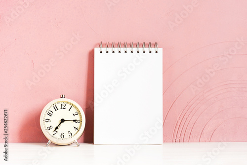 Photo  Alarm clock and blank notepad on the wooden white table