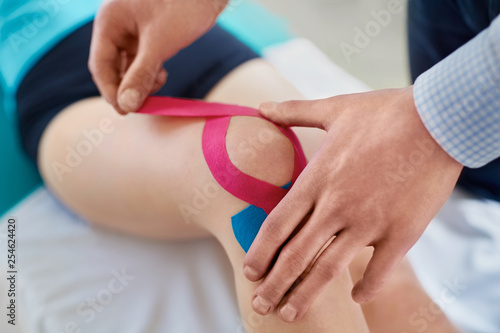 Fotografía  Kinesiology. Therapist taping knee with physio tape