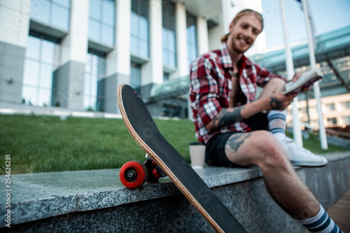 Foto  Selective focus of a skateboard with a cheerful man in the background