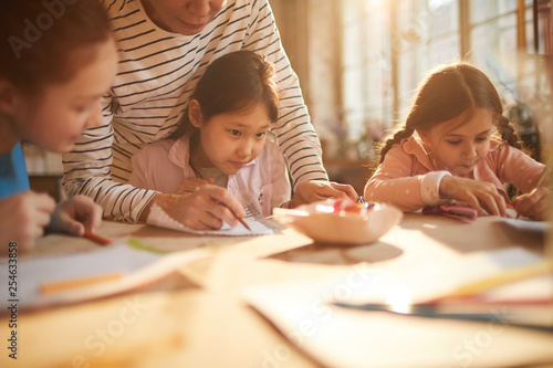 Portrait Of Cute Asian Girl Drawing Picture In Art Class For
