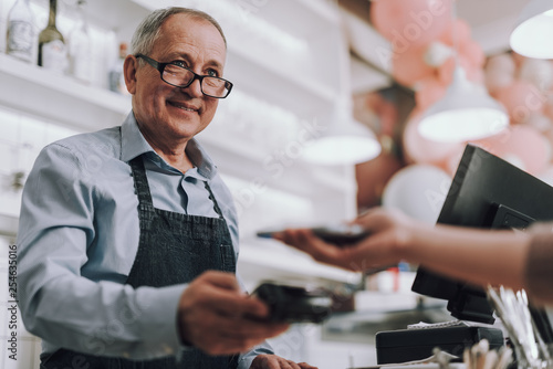 Photo Friendly shop owner in glasses accepting payment from customer