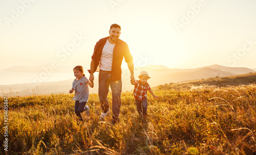 Spoed Foto op Canvas Hoogte schaal happy family father and children in nature at sunset.