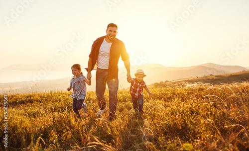 szczęśliwy ojciec rodziny i dzieci w przyrodzie o zachodzie słońca.