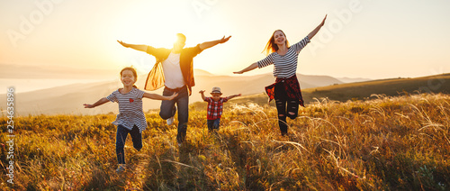 Fototapeta Happy family: mother, father, children son and daughter on sunset. obraz na płótnie