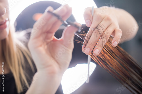Fotografia Close up of clean hair with scissors in arms of stylist