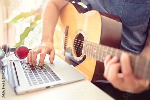 Musician playing acoustic guitar and recording music on computer Fototapet