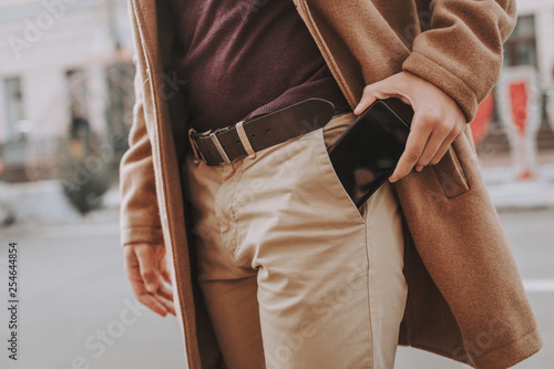 Young man getting smartphone out of his pocket Canvas Print