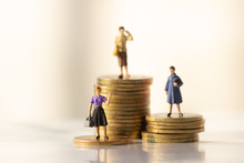 Concept Of Retirement Money Plan And Savings Growth. Old And Young Woman Stand On Stacks Of Gold Coins Isolated On White And Orange Background.