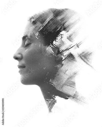 Paintography. Double exposure portrait of a young woman's profile combined with handmade painting with a texture of brushstrokes disappearing into her face. Black and white