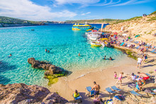 Comino, Malta - November, 2018: Tourists Crowd At Blue Lagoon To Enjoy The Clear Turquoise Water On A Sunny Summer Day With Clear Blue Sky And Boats On Comino Island, Malta.