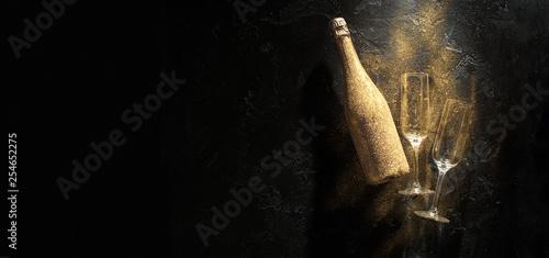 Fotografie, Obraz  Photo of golden champagne bottle, two wine glasses on black stone background