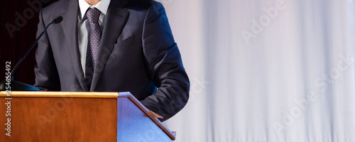 Photo Speech of an abstract man in a suit on stage at the stand for performances