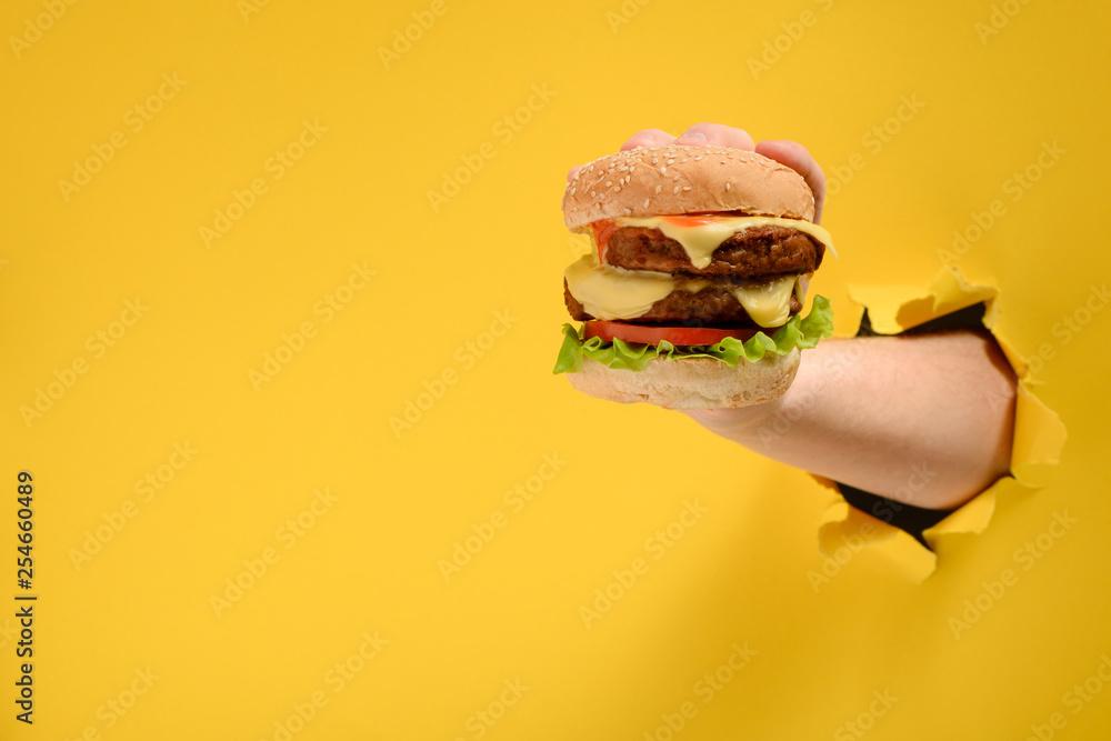 Fototapety, obrazy: Hand taking a big burger